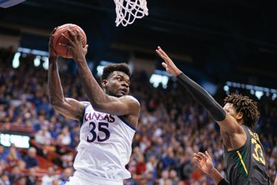 Senior center Udoka Azubuike rebounds the ball, holding it to his right above his head away from a Baylor guard