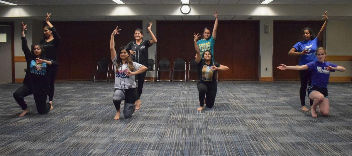Eight dancers perform a Bollywood fusion dance routine
