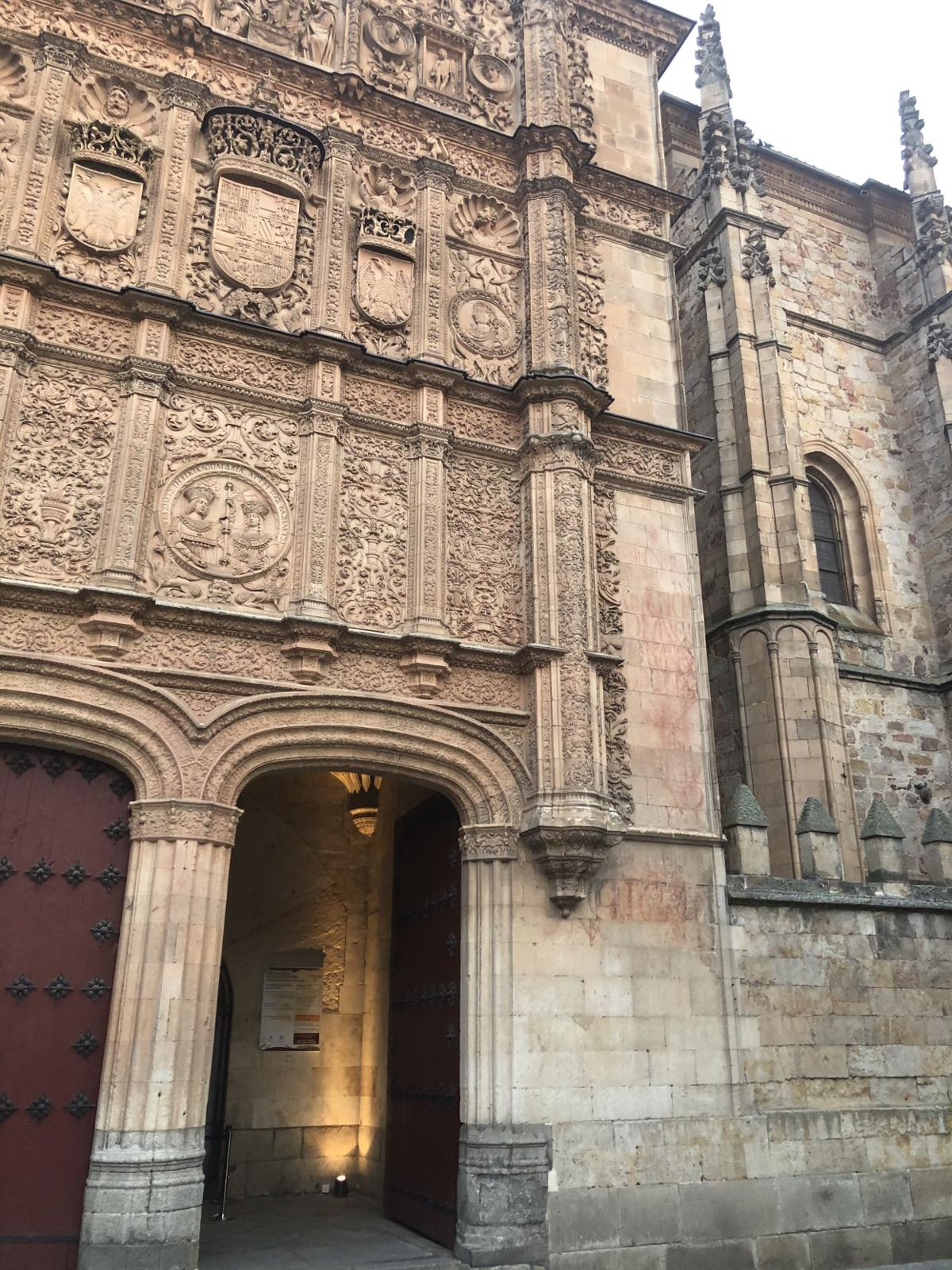 The facade of the University of Salamanca has two archways below ornate relief sculptures in the exterior walls
