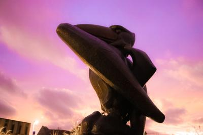 Strong Hall Jayhawk Statue in front of purple sunset