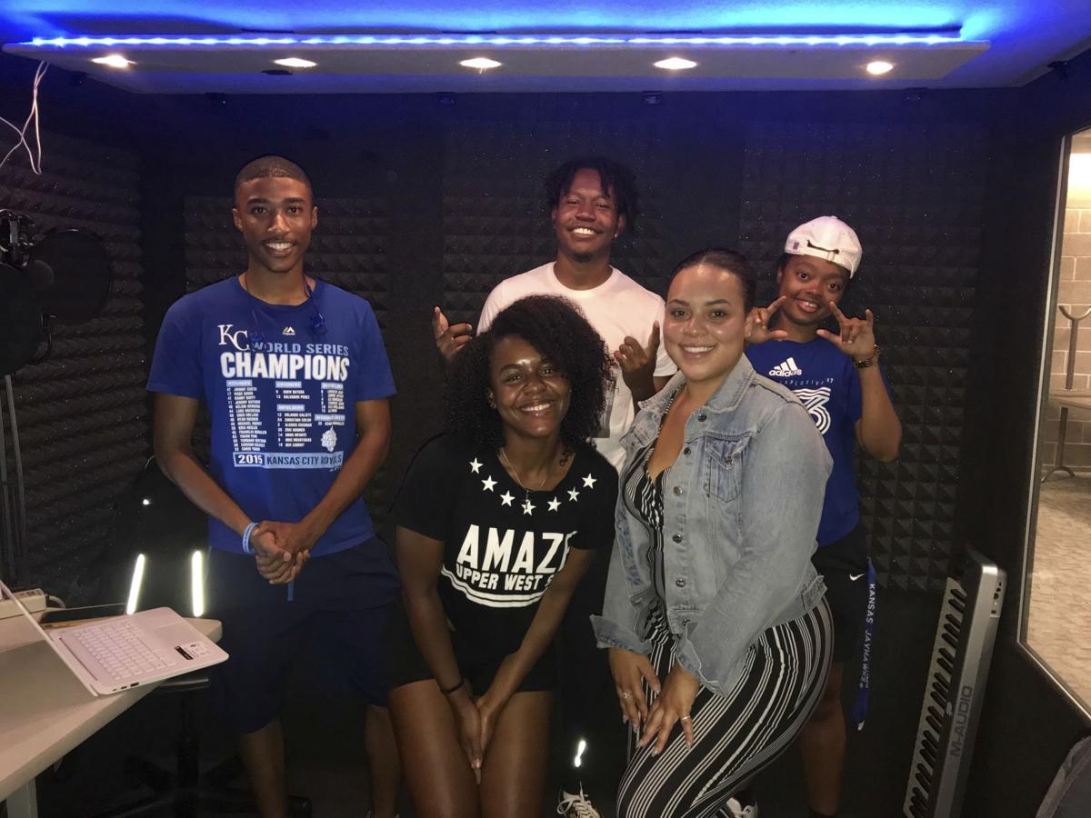 "Five members of the podcast ""Black Talk"" stand in their recording booth"