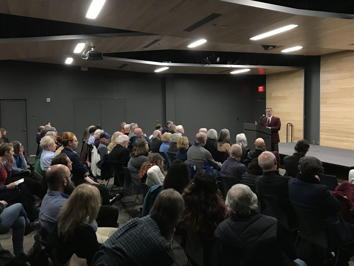Richard Godbeer lectures in front of a crowd of roughly 30 people at the Lawrence Public Library