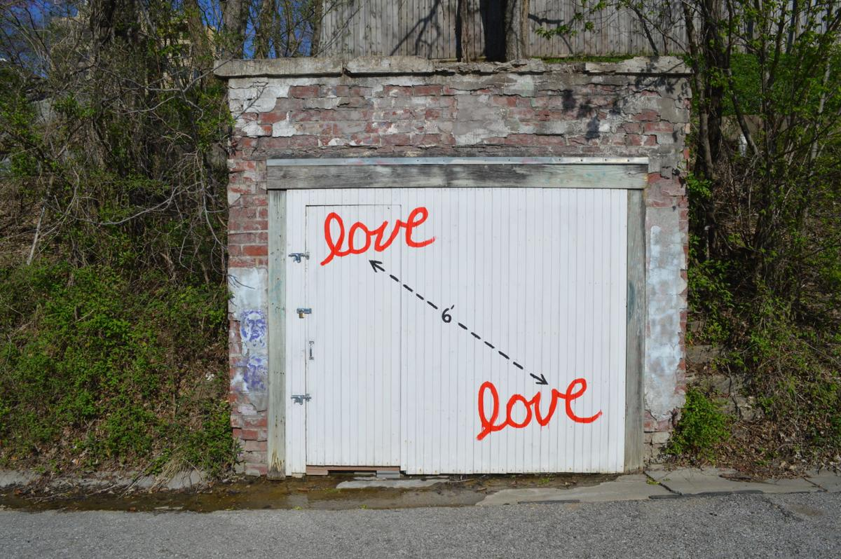 "A painting on a door displays two words of ""love"" separated by a line that measures 6 feet"