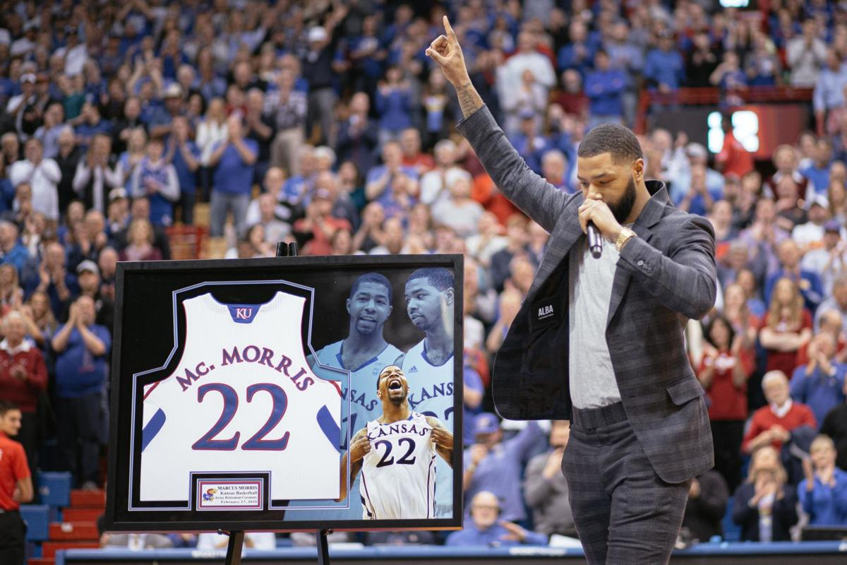 Marcus Morris holds one finger up while his other hand holds a mic. Next to him is his framed Mc. Morris jersey