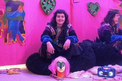 Brooke Metz sits in her exhibit.