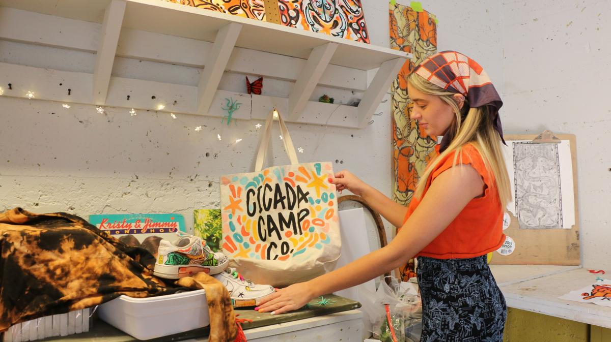 """A woman holds up a tote bag that reads """"Cicada Camp Co."""""""