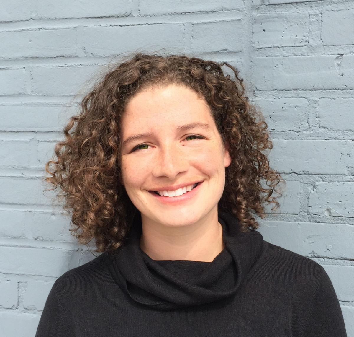 Industrial design professor Betsy Barnhart smiles as she stands in front of a wall