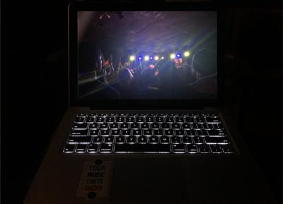 A computer keyboard lights up in the dark as the screen displays a concert at The Bottleneck