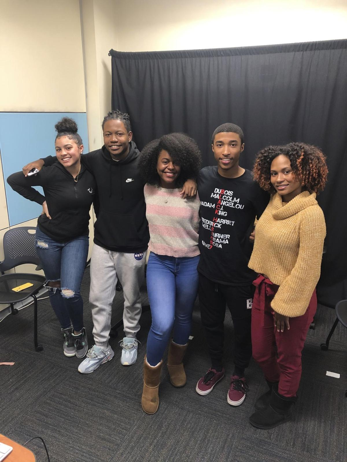 "Five members of the podcast ""Black Talk"" stand in their podcast studio"