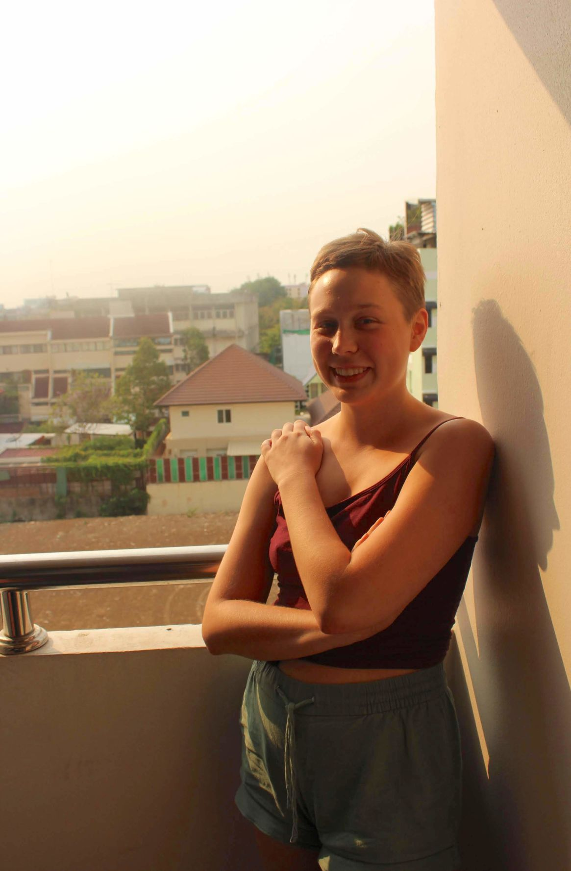 Katie Counts smiles in the sunshine on a balcony in Bangkok