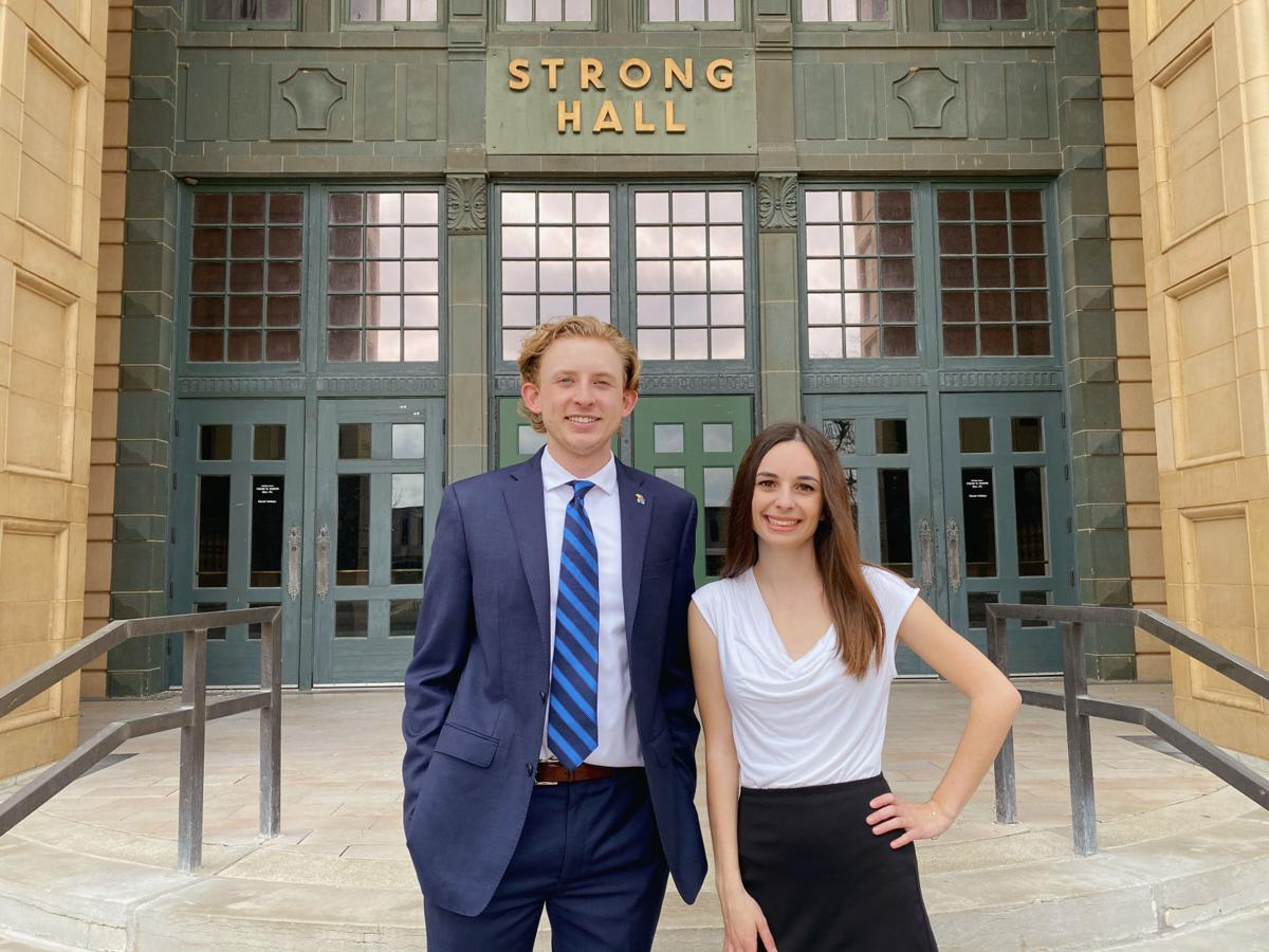 William Wilk and Isabella Southwick pose together in front of the doors of Strong Hall