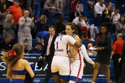 Junior forward Tina Stephens hugs her teammate as she stands on the court of Allen Fieldhouse