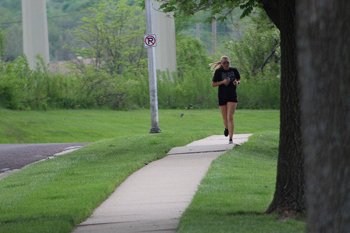 A woman runs down the sidewalk beside a tree