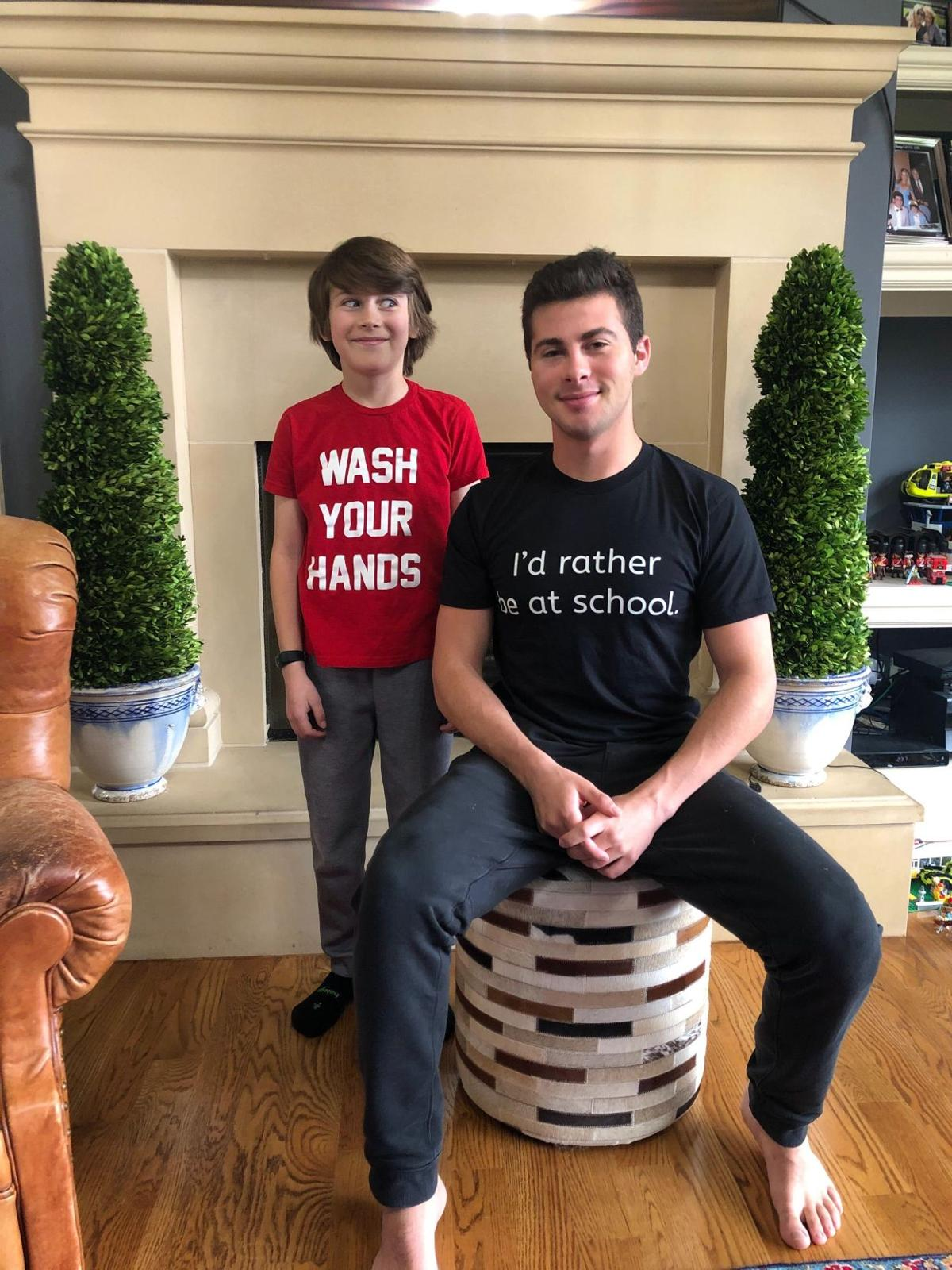 "Two brothers smile at the camera. They wear t-shirts with the sayings, ""Wash Your Hands"" and ""I'd rather be at school"""