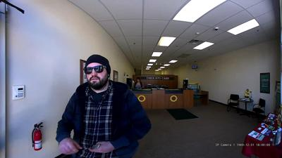 Security footage shows a man in sunglasses leaving Check Into Cash with a wad of money in his hands