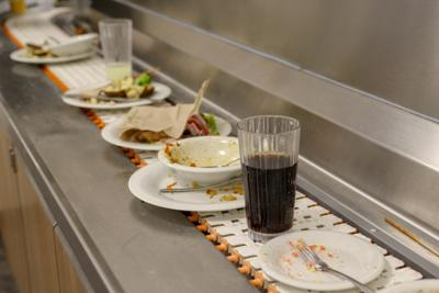 A trash conveyor belt in the South Dining Commons carries trash and dishes into the dining facility's kitchen (copy)
