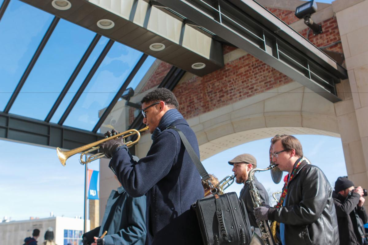 A man plays the trumpet in front of other band members under the entryway to the Kansas Union.