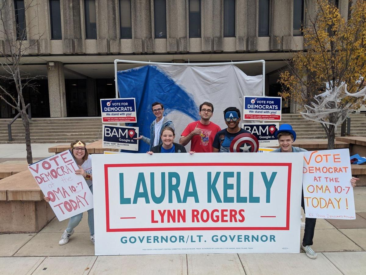 A group of students table for Laura Kelly with posters in front of Wescoe Hall