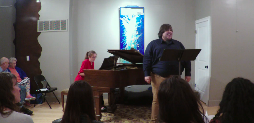 A man sings in front of a music stand as he is accompanied by a woman playing the piano