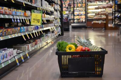 A basket filled with produce sits on the floor in the granola bar aisle at Dillons