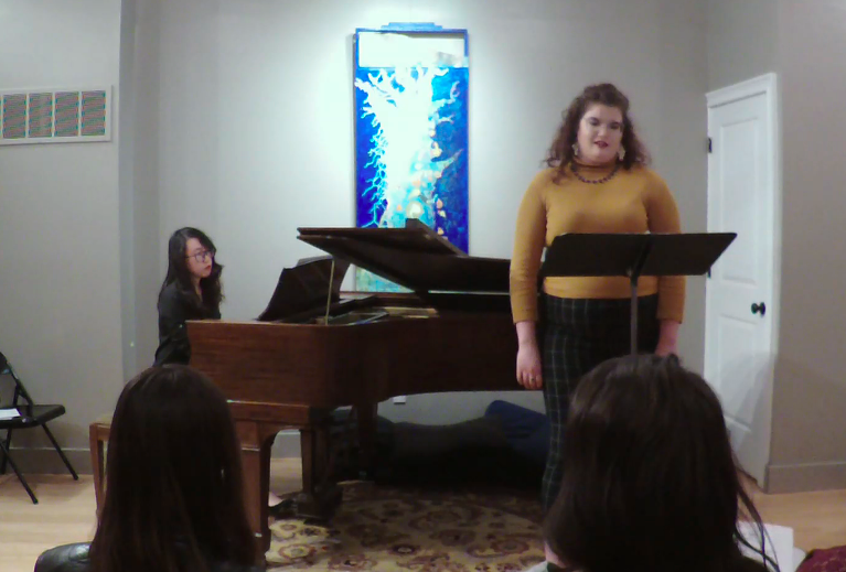 A woman sings in front of a music stand as she is accompanied by a woman playing the piano