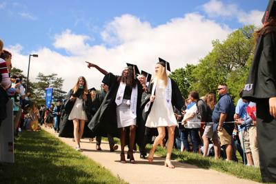Students in graduation caps and gowns walk down the hill as crowds of friends and families line the sidewalk