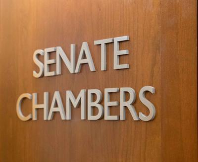 Student Senate is located in the Kansas Union, where the words 'Senate Chambers' decorate wood walls