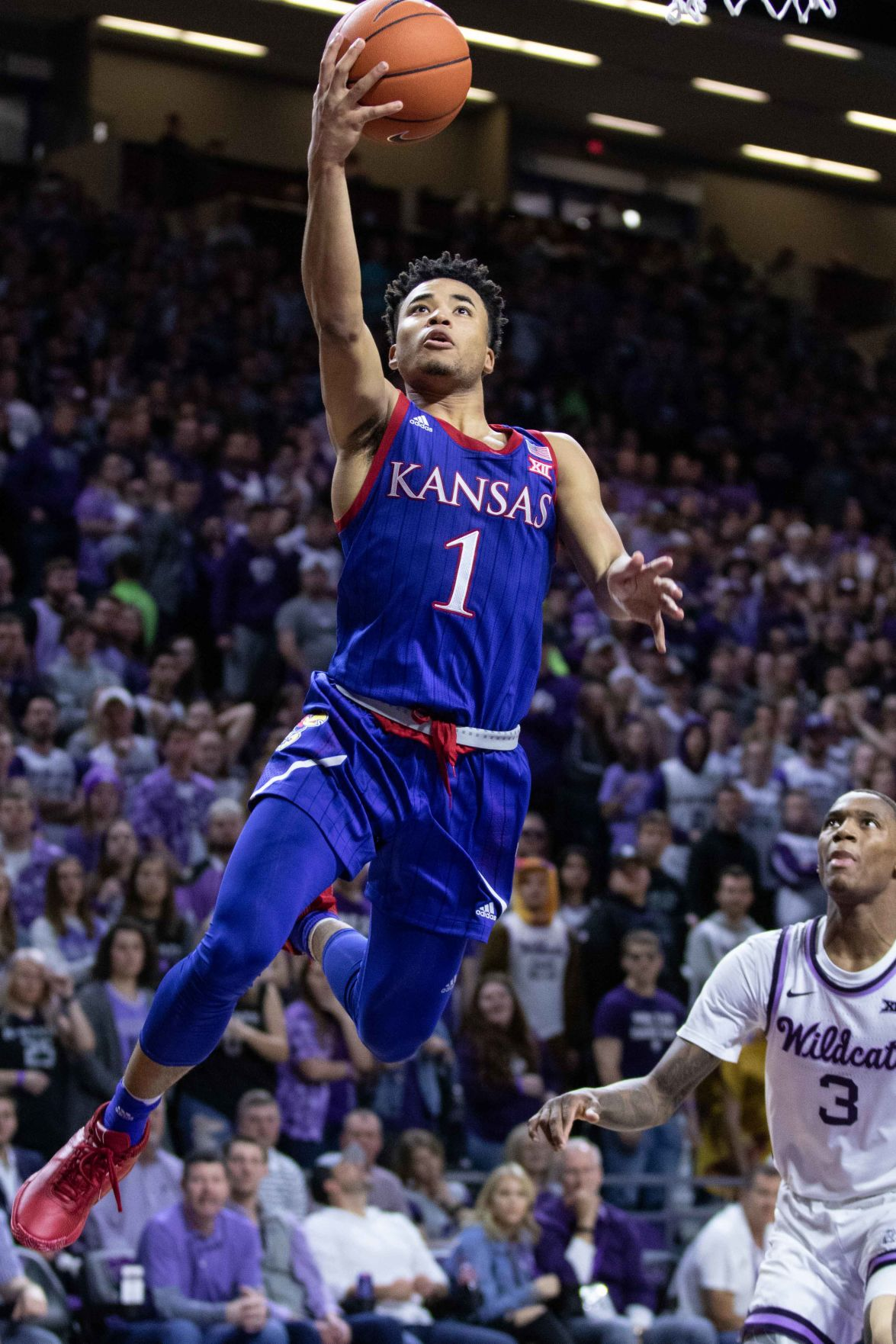 Devon Dotson lifts the basketball above his head as he jumps up toward the rim