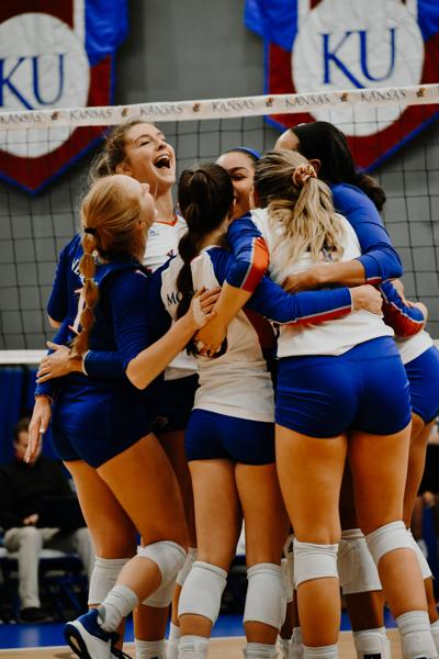 The Kansas volleyball team embraces after defeating Texas Tech