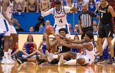 Sophomore guard Ochai Agbaji fights to grab the basketball as he sits on the floor of Allen Fieldhouse
