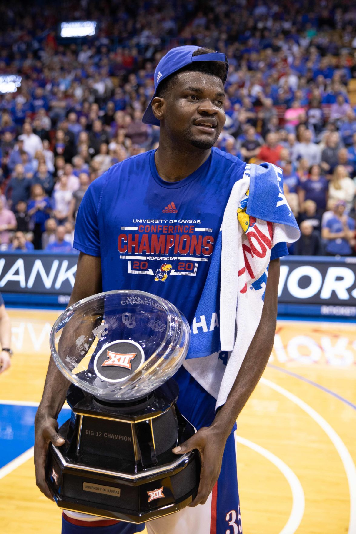 Udoka Azubuike holds the Big 12 Championship trophy on the court in Allen Fieldhouse