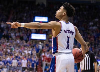 Devon Dotson points to his left as he dribbles the ball in his right hand