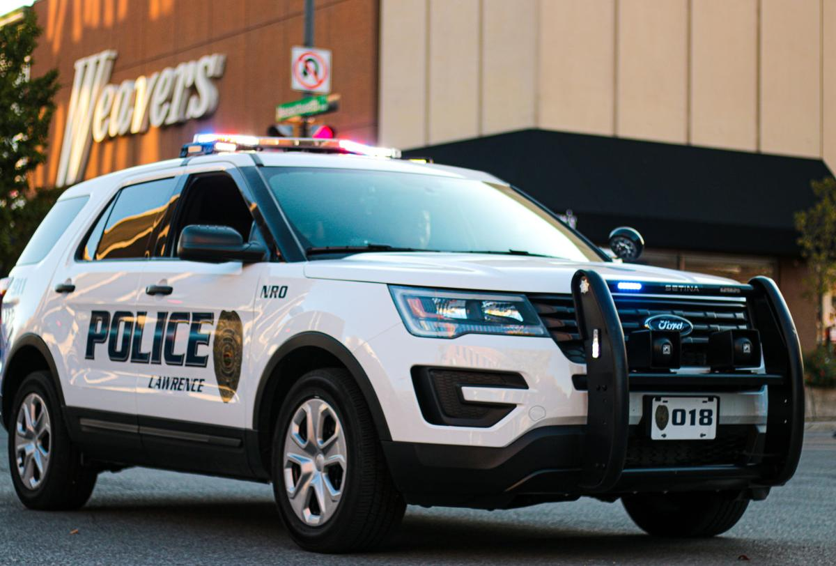 A Lawrence Police Department S.U.V. drives past Weavers Department Store on Massachusetts Street