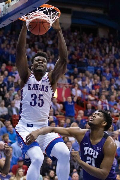 Udoka Azubuike jumps up and grabs the hoop as the basketball swishes through the net