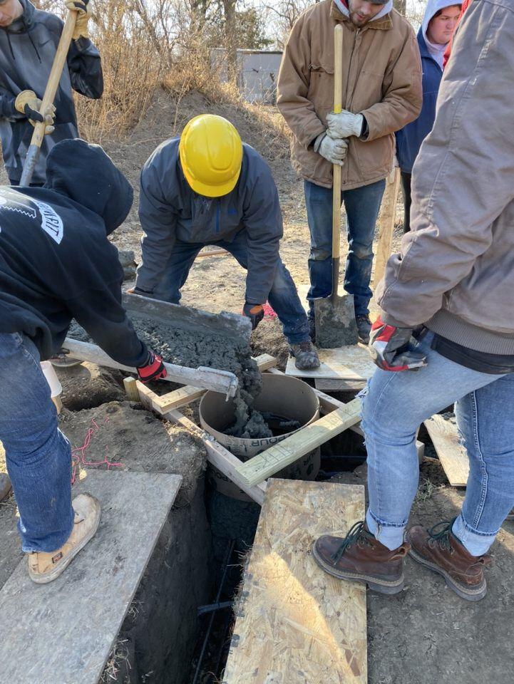 Students pour concrete