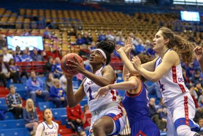 Junior forward Tina Stephens clasps the basketball in her hands as she goes in for a layup in Allen Fieldhouse