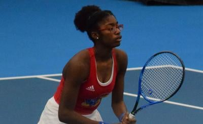 Malkia Ngounoue squats in front of the net and holds the racket as she waits for the serve