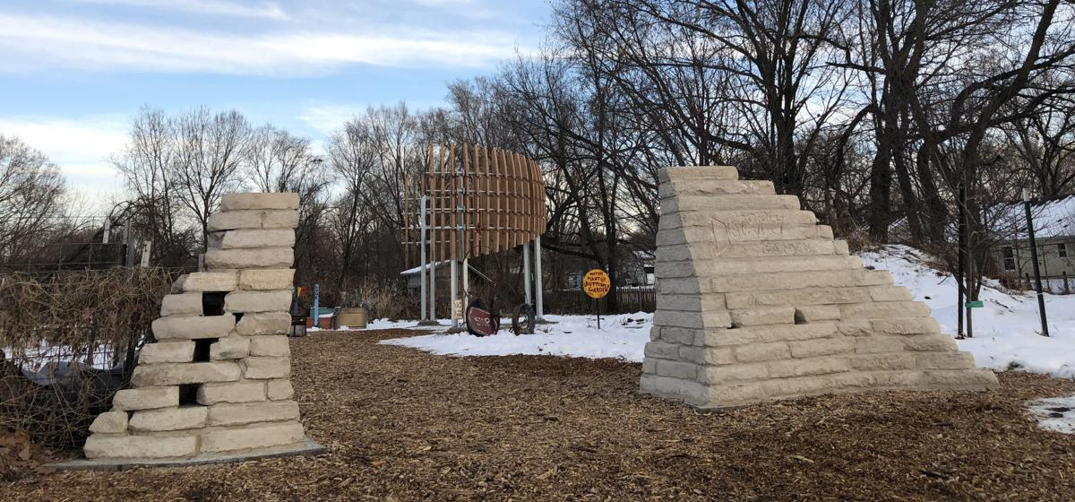 Limestone structures frame the entrance to a park with a large wooden pavilion in the background