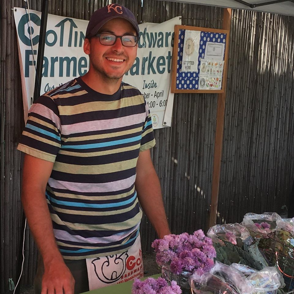 A man smiles at the camera while selling goods at a farmer's market