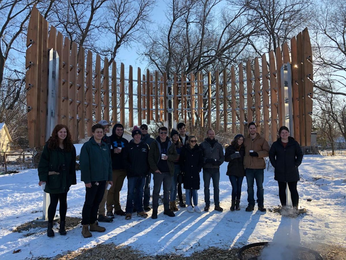 Students stand in front of a pavilion structure in a park