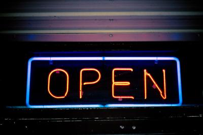 A neon sign glows the word 'Open'
