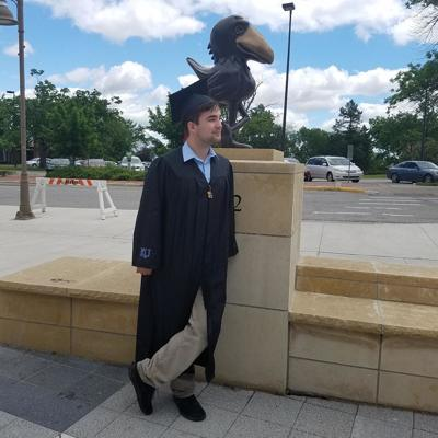 Josh McQuade stands in front of a bronze Jayhawk statue while wearing a graduation cap and gown