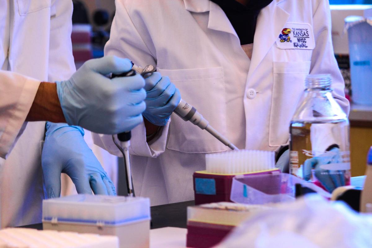 Two people in lab coats wear gloves as they test vaccines