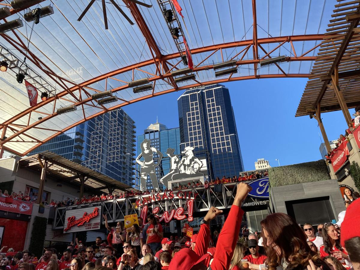 A crowd of Kansas City Chiefs fans gather beneath the city skyline to celebrate the Super Bowl at Power & Light