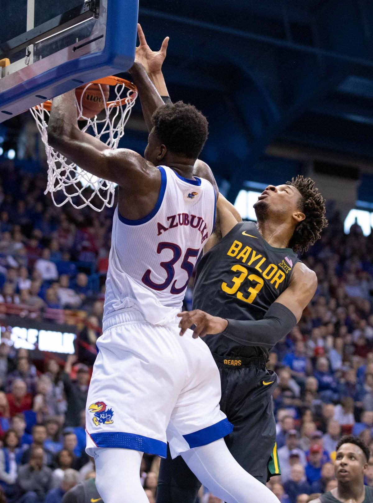 Senior center Udoka Azubuike slams the ball in the net while a Baylor guard tries to block