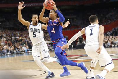 Devonte' Graham holds the basketball above his head as two Villanova players surround him