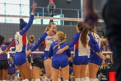 The Kansas volleyball team jumps up and down excitedly after scoring a point against K-State