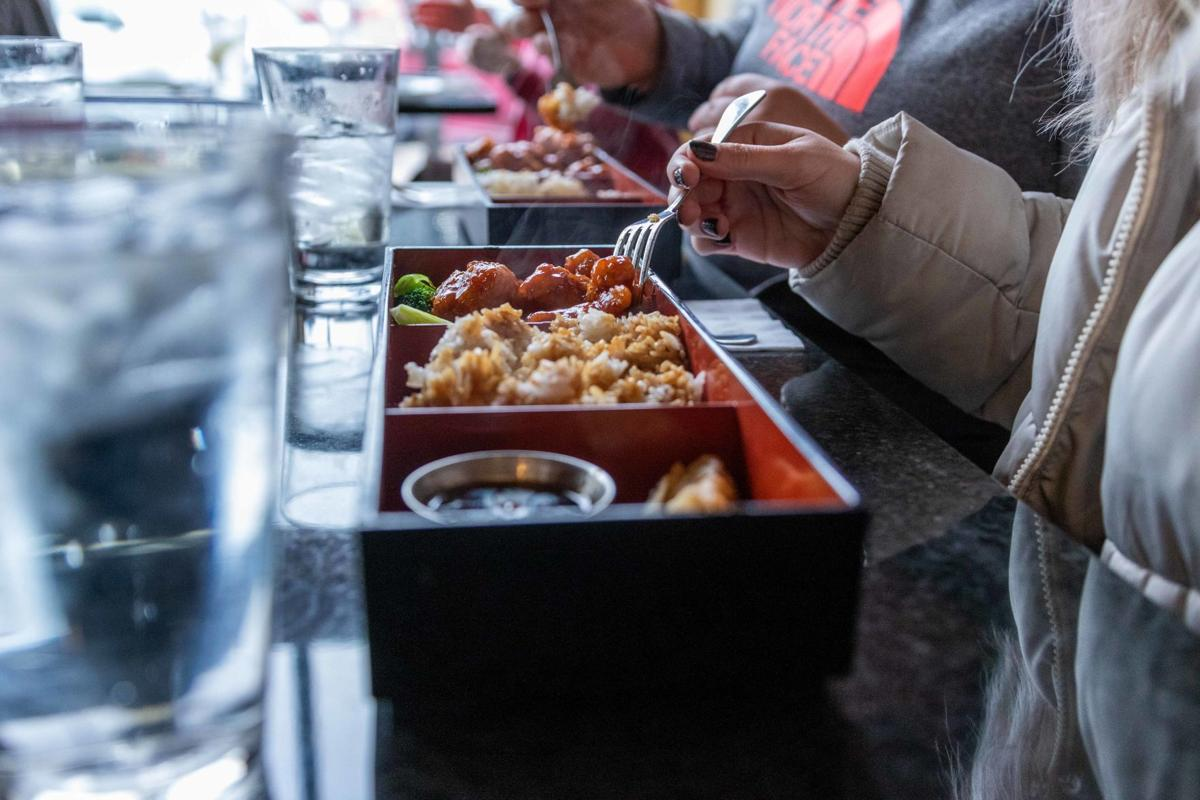 Asian fusion food lines the table as customers eat at Encore Cafe