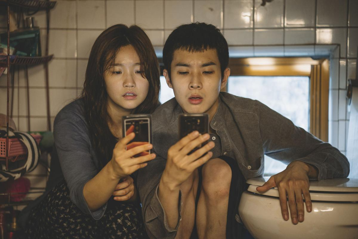 Two young people look at their phones while crouching down and leaning against a toilet