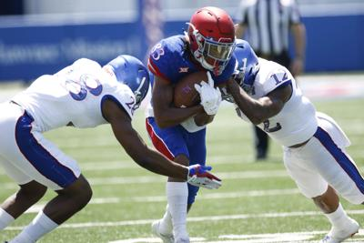 Kwamie Lassiter II carries the football close to his chest as two other Kansas players come at him from left and right